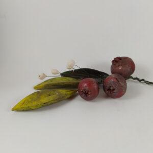 Τρία ρόδια κόκκινα (μεταλλιζέ), τέσσερα λευκά μπουμπούκια και τρία φύλλα με πράσινες αποχρώσεις (μεταλλιζέ) όλα κεραμικά δεμένα με σύρμα σε μπουκέτο