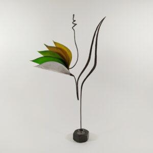 """Γλυπτό """"λουλούδι-πουλί"""" μονοκοντυλιά μεταλλικό με χάρτινα """"πέταλα-ουρά"""" σε πράσινες και κίτρινες αποχρώσεις στηριζόμενο σε λεπτό μεταλλικό άξονα"""